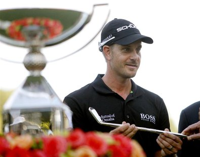 Henrik Stenson of Sweden accepts a replica of a Bobby Jones putter as he stands beside the FedExCup trophy after winning the the Tour Champi
