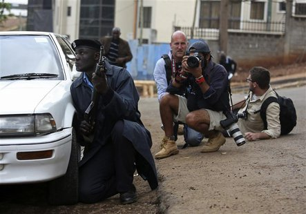 A policeman and photographers take cover after hearing gun shots near the Westgate shopping centre in Nairobi September 23, 2013. REUTERS/Ka