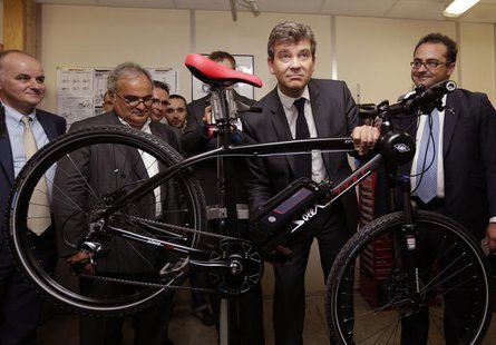 French Minister for Industrial Recovery Arnaud Montebourg (2ndR) and Gregory Trebaol (R), President of Easybike, stand with a prototype Sole