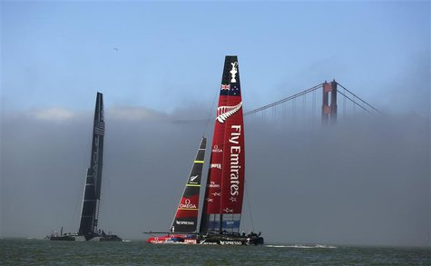 Oracle Team USA (L) sails against Emirates Team New Zealand near the Golden Gate Bridge during the 34th America's Cup yacht sailing race in