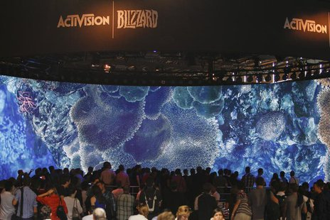 Visitors look at a presentation at the ActiVision Blizzard exhibition stand during the Gamescom 2013 fair in Cologne August 21, 2013. REUTER