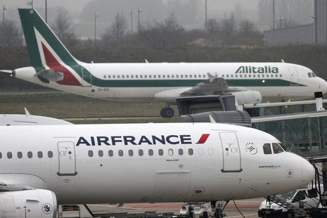 An Alitalia plane passes an Air France plane on the tarmac of Charles de Gaulles International Airport in Roissy near Paris, January 8, 2013
