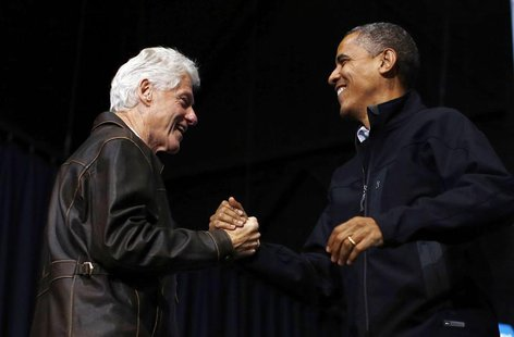 Former U.S. President Bill Clinton (L) introduces U.S. President Barack Obama during a campaign rally in Bristow, Virginia, November 3, 2012