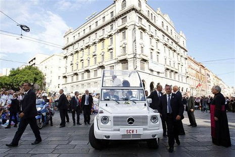 Bodyguards escort Pope Francis as the faithful welcome his arrival in his Pope-mobile for a meeting with youths in Largo Carlo Felice in Cag