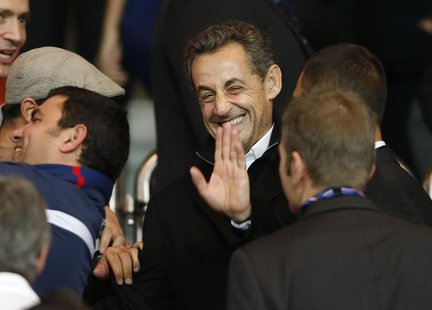 Former French President Nicolas Sarkozy waves as he arrives to attend the Paris St Germain and Monaco French Ligue 1 soccer match at the Par