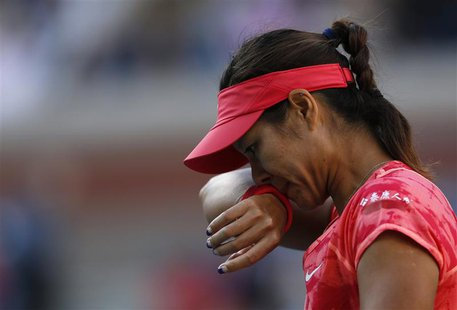 Li Na of China wipes her face during her match against Serena Williams of the U.S. at the U.S. Open tennis championships in New York Septemb