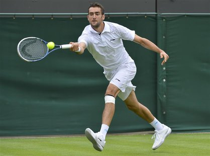 Marin Cilic of Croatia hits a return to Marcos Baghdatis of Cyprus in their men's singles tennis match at the Wimbledon Tennis Championships