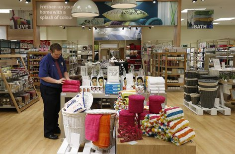 An employee straightens a display in the home ware department at a Tesco Extra supermarket in Watford, north of London August 8, 2013. REUTE