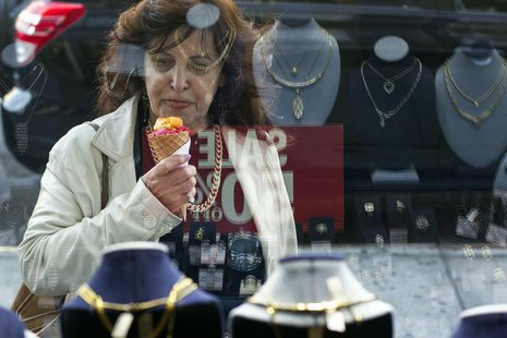 A woman eats ice cream as she looks at the display in the window of a Gold Standard jewellery store that specializes in purchasing raw gold