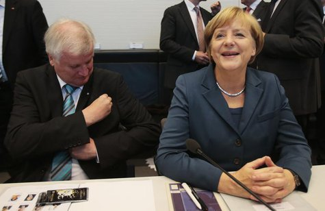 Bavarian state Premier Horst Seehofer and German Chancellor Angela Merkel await the start of a parliamentary group meeting of the Chirstian