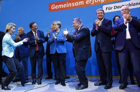 German Chancellor and leader of the Christian Democratic Union (CDU) Angela Merkel (C) and CDU party fellows sing as they celebrate after fi