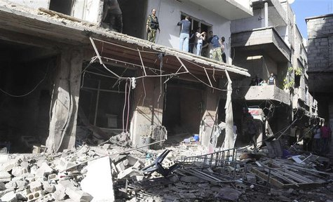 People gather around wreckage after a car bomb exploded in the Tadamon district of southern Damascus, in this handout photograph released by