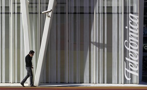 A man speaks by a mobile next to Telefonica's tower in Barcelona January 30, 2013. REUTERS/Albert Gea