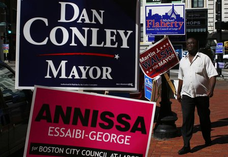 A pedestrian walks by campaign signs outside a polling station in Boston, Massachusetts September 24, 2013. REUTERS/Brian Snyder