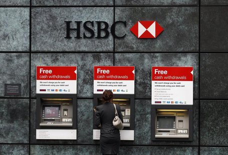 A woman uses a cash point machine at a HSBC bank in the City of London February 28, 2011. REUTERS/Andrew Winning