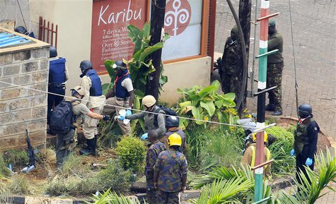 Foreign forensic experts, flanked by Kenyan military personnel, check the perimeter walls around Westgate shopping mall in Nairobi September