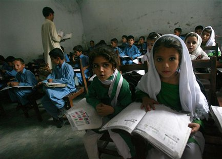 Female students Shaista (R), 12, and Rabia (L), 10, read aloud while taking part in class in Buner district about 220 km (137 miles) by road