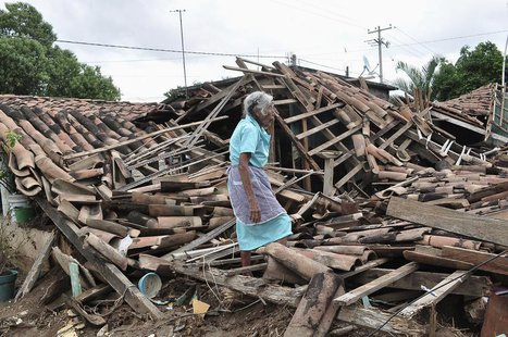 A woman stands amidst the debris of her destroyed home in Agua Caliente, on the outskirts of Acapulco September 20, 2013. REUTERS/Claudio Va