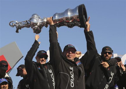 Oracle CEO Larry Ellison lifts the America's Cup with members of the Oracle Team USA after winning the overall title of the 34th America's C