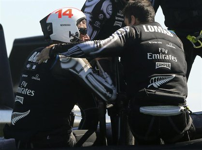 Emirates New Zealand skipper Dean Barker (L) is consoled by a crew member after losing the winner-take-all Race 19 of the 34th Americas Cup