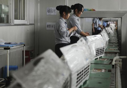 Employees make air-conditioners along a production line at a factory of Gree Electric Appliances in Hefei, Anhui province August 6, 2011. RE