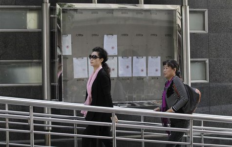 Singer Meng Ge (L) walks into a court ahead of a verdict hearing of her son in Beijing, September 26, 2013. REUTERS/Stringer