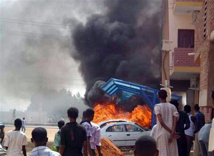 People look at burning cars during protests over fuel subsidy cuts in Khartoum September 25, 2013. REUTERS/Stringer