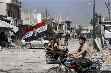 Forces loyal to Syria's President Bashar al-Assad carry the national flag as they ride on motorcycles in Qusair, after the Syrian army took control from rebel fighters, in this file picture taken June 5, 2013.  REUTERS/Mohamed Azakir/Files