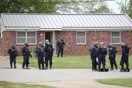 Federal officials stand outside the house of Paul Kevin Curtis while searching for evidence in Corinth, Mississippi April 18, 2013. REUTERS/