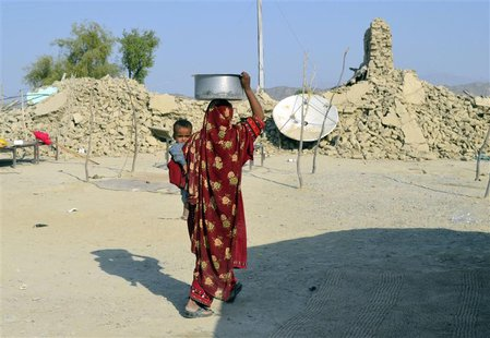 A survivor of an earthquake carries a pot on her head filled with drinking water as she walks near the rubble of a mud house after it collap