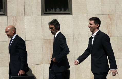 Barcelona's soccer player Lionel Messi (R) leaves after answering charges of tax evasion in a court in Gava September 27, 2013. REUTERS/Albe