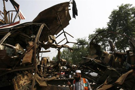 A rescue worker stands near the damaged bus after it was hit by a bomb attack on the outskirts of Peshawar September 27, 2013. REUTERS Khura
