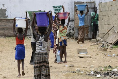 People carry containers of water from a communal source in Senegal's capital Dakar September 27, 2013. REUTERS/Ricci Shyrock