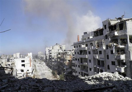 Smoke rises from buildings after what activists say was an air strike by forces loyal to Syrian President Bashar Al-Assad in Homs September