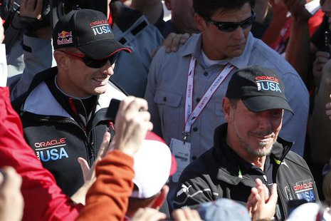 Oracle Team USA Skipper James Spithill (L) and Oracle CEO Larry Ellison walk pass spectators after the team successfully defended the 34th A