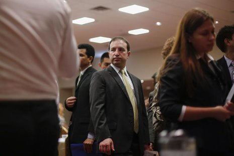 A man waits in line to talk to recruiters while attending a job fair in New York, June 11, 2013. REUTERS/Lucas Jackson