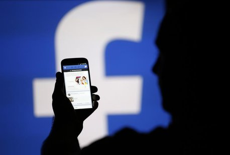 A man is silhouetted against a video screen with an Facebook logo as he poses with an Samsung S4 smartphone in this photo illustration taken