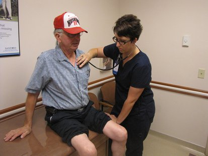 Afton Sue Zediker, clinical supervisor at Sanford Orthopedic and Sports Medicine, assesses patient Ronald Mueller prior to receiving steroid injections in his knees. Zediker will graduate in May with a bachelor's degree in nursing through SDSU's Registered Nurse Upward Mobility program.