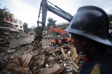 Rescue crew members watch as others use excavators to scour the debris for survivors at the site of a collapsed residential building in Mumb