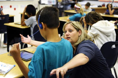 Fourth grade teacher Alicia Schoenborn works with a student at Mahnomen Elementary School in Mahnomen, Minnesota September 26, 2013. REUTERS