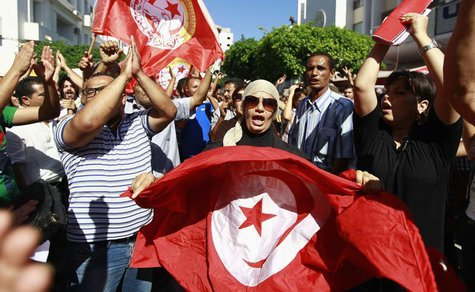 Anti-government protesters wave Tunisian flags as they rally for the dissolution of the Islamist-led government in Sfax, 170 miles (270 km)