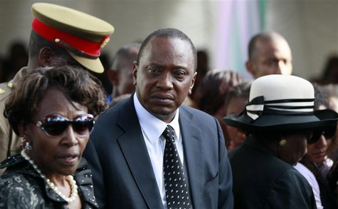 Kenyan President Uhuru Kenyatta (C) joins his relatives as he attends the burial of his nephew Mbugua Maina and Maina's fiancee Rosemary Wah