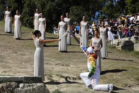 Greek actress Ino Menegaki, playing the role of High Priestess, passes the Olympic flame to Greek skier Yannis Antoniou, the first torchbear