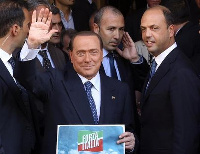 Silvio Berlusconi waves to supporters next to People of Freedom (PDL) Secretary Angelino Alfano (R) while showing the logo of his re-launche