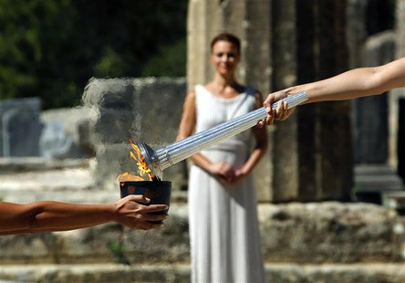 Greek actress Ino Menegaki (R), playing the role of High Priestess, passes the Olympic Flame to a priestess holding a cauldron (L) during a