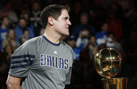 Dallas Mavericks owner Mark Cuban holds the Larry O'Brien Championship trophy during a ceremony before their NBA basketball game with the Mi