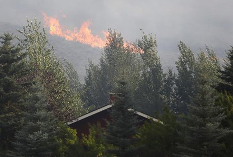 Flames are visible near a home in the evacuated Golden Eagle subdivision as the Beaver Creek wildfire rages outside Hailey, Idaho August 16,