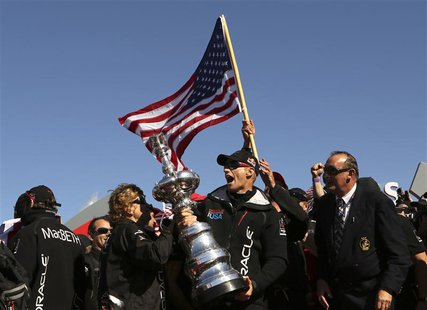 Skipper James Spithill celebrates with the America's Cup with members of the Oracle Team USA after winning the overall title of the 34th Ame