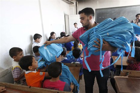 A man distributes bags donated from UNICEF to young students in Raqqa, eastern Syria September 29, 2013. The distribution of around 60,000 b