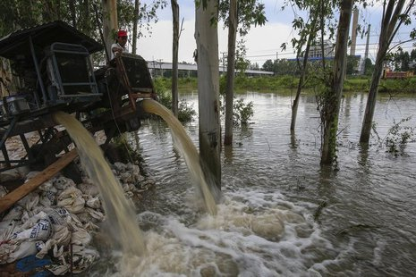A man looks on as water is pumped out of a canal near 304 Industrial Estate at Srimahaphot district in Prachin Buri September 29, 2013. REUT